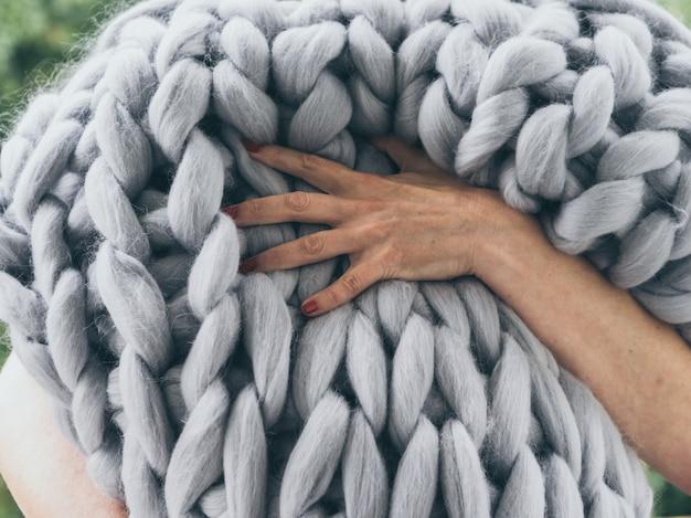 Grande coperta in maglia di lana merino fatta a mano. primo piano della coperta lavorata a maglia, priorità bassa della lana merino
