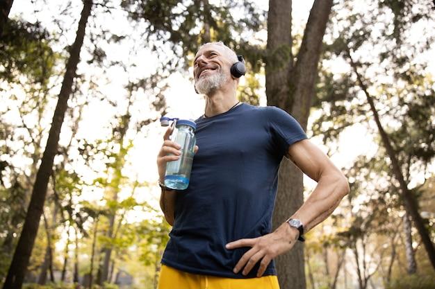 Buon uomo atletico che va a fare jogging nella foresta