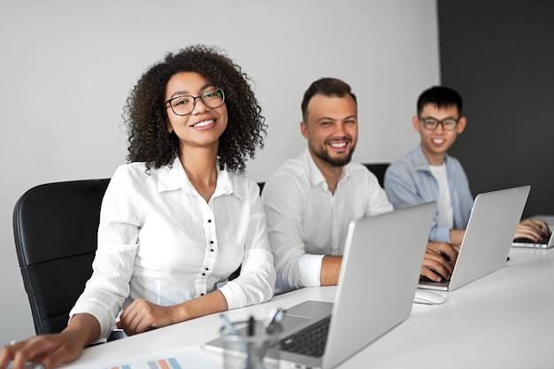Allegra femmina nera sorridente e guardando la fotocamera mentre si lavora con i colleghi maschi multirazziali con i laptop nel posto di lavoro contemporaneo