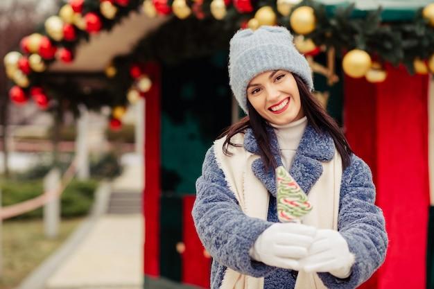 Allegra donna bruna indossa un cappello lavorato a maglia e un cappotto invernale che tiene caramelle vicino alla strada natale con le palle. spazio per il testo