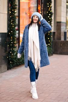 Allegra donna bruna indossa berretto rosa chiaro lavorato a maglia e sciarpa che cammina in città decorata con ghirlande. spazio per il testo