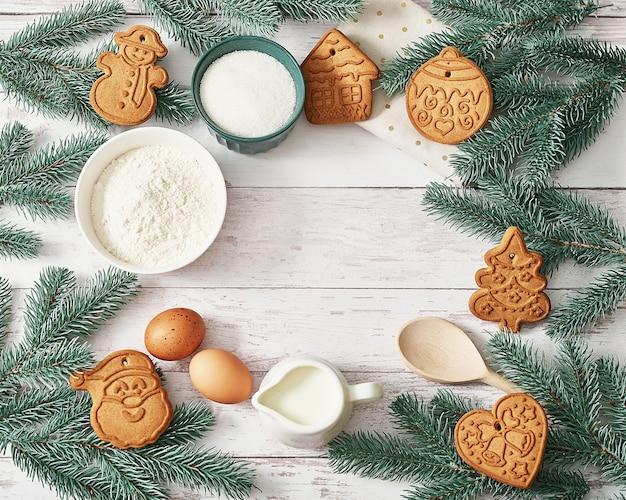 Buon natale sfondo gustosi biscotti allo zenzero fatti in casa. ingredienti per cucinare la cottura, utensili da cucina, pan di zenzero. cartolina d'auguri di felice anno nuovo. tavolo di natale. abete, pino.