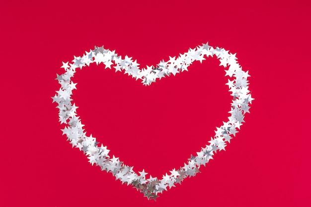 Buon natale grande cuore fatto di stelle d'argento su sfondo rosso festivo. buon anno 2022