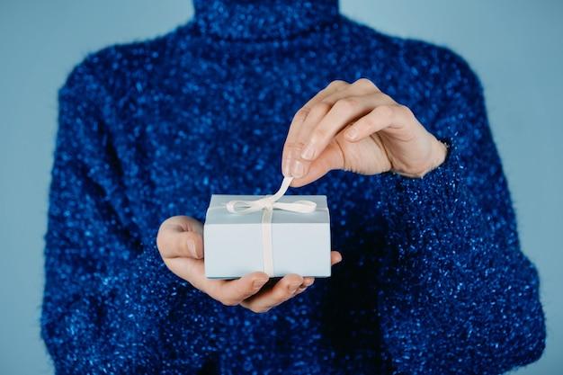 Buon natale carta hew anno natale compleanno banner mani femminili in maglione blu che tengono regalo artigianale