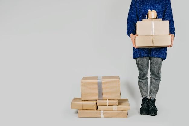 Merry christmas card hew anno natale compleanno banner donna in maglione blu che tiene molte scatole regalo artigianali