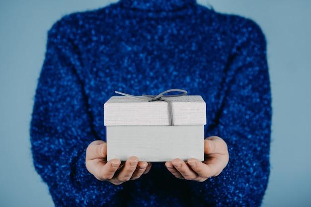 Buon natale carta capodanno natale compleanno banner mani femminili in maglione blu che tengono regalo artigianale
