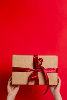 Buon natale. le mani dei bambini tengono una confezione regalo legata con un nastro rosso su uno sfondo rosso. verticale. un posto per il testo. foto di alta qualità