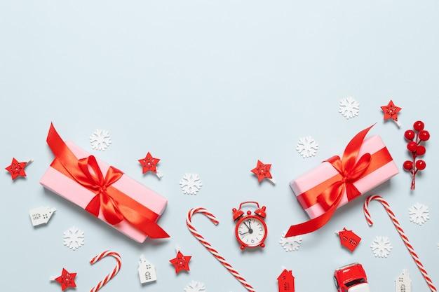 Composizione di buon natale con scatole di carta rosa, nastri rossi, bastoncini di zucchero, candele e fiocchi di neve