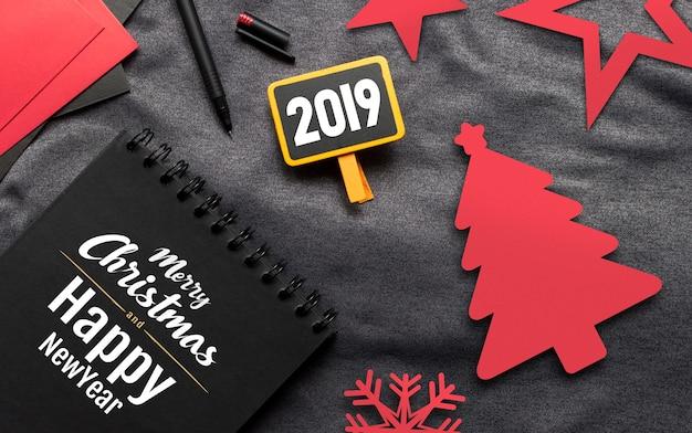 Concetto di buon natale, libro nero, carta rossa e penna sul panno grigio