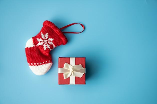 Concetto di buon natale: scatola rossa presente e calzino neonato bambino rosso su sfondo blu