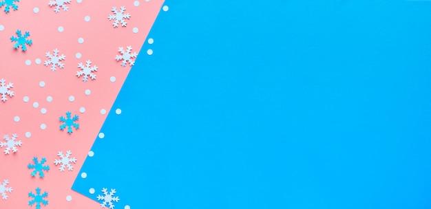 Buon natale! la carta creativa piatta giaceva in rosa, blu e bianco con fiocchi di neve