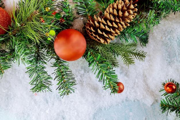 Buon natale palla decorativa sulla neve con sfondo di tempo di natale di cono di pino ramo