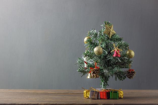 Fondo di concetto dell'albero di abete di buon natale contenitore di regalo attuale e decorazione & ornamento festivi su legno rustico moderno contesto e spazio di spazio grigi della copia per la fonte ed i testi creativi di progettazione.