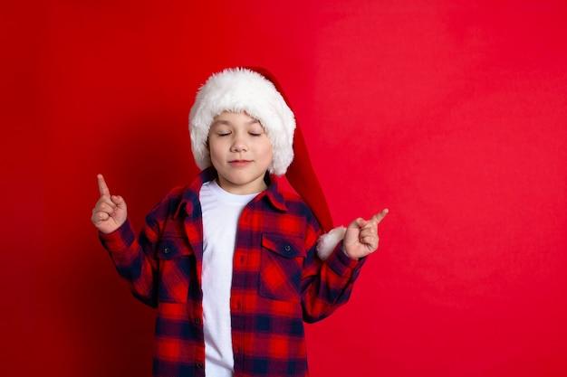 Buon natale. un ragazzo divertente con un berretto da babbo natale balla su uno sfondo rosso. posto per il testo. foto di alta qualità