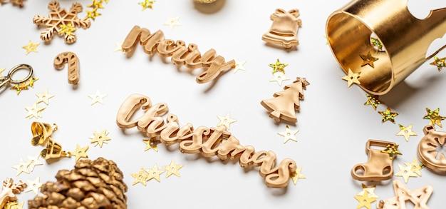 Testo lucido dell'oro di buon natale con oggetti di decorazione di natale di lusso sulla tavola bianca