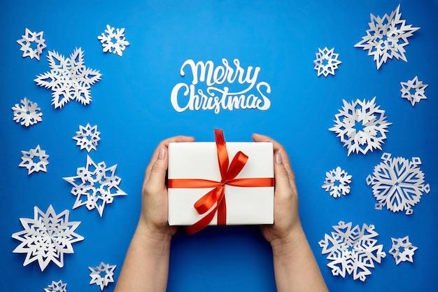Cartolina d'auguri di buon natale con scatola regalo e fiocchi di neve di carta sull'azzurro