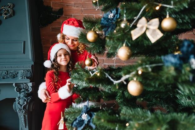 Buon natale e buone feste! la bella madre con la piccola figlia in costumi di natale trascorre del tempo insieme vicino all'albero di natale.