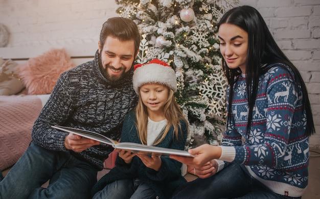 Buon natale e buone feste mamma, papà e figlia carina si scambiano regali. genitore e bambino che hanno divertimento vicino all'albero di natale al chiuso. mattina natale.