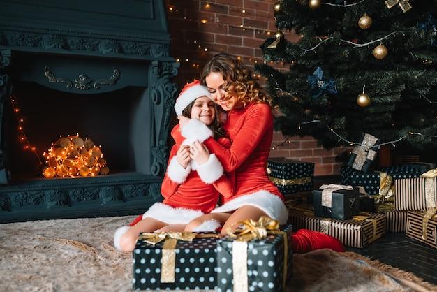 Buon natale e buone feste! mamma allegra e la sua ragazza carina figlia in costumi natalizi che si scambiano i regali.