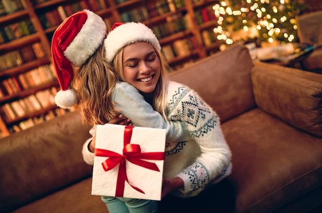 Buon natale e buone feste! mamma allegra e sua figlia carina che si scambiano regali. genitore e bambino che si divertono vicino all'albero al chiuso. famiglia amorevole con regali in camera.