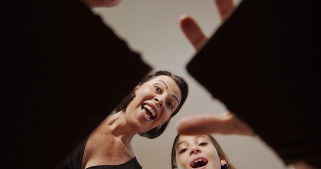 Buon natale e buone feste! mamma allegra e sua figlia carina che aprono un regalo di natale. genitore e bambino che si divertono al chiuso. vista dall'interno della scatola.