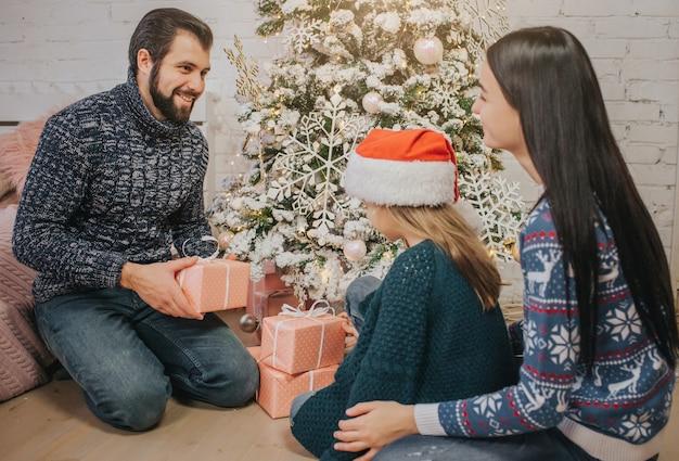 Buon natale e buone feste madre allegra, padre e figlia carina che si scambiano doni.