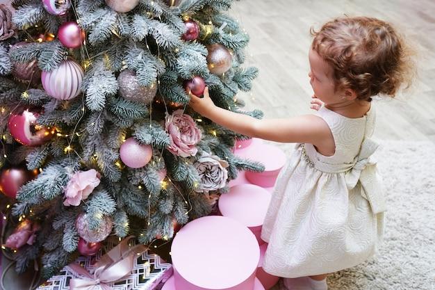 Buon natale e buone feste, bambina carina sta decorando l'albero di natale al chiuso.