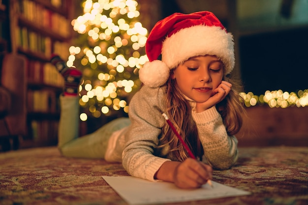 Buon natale e buone feste! la bambina sveglia del bambino scrive la lettera a babbo natale vicino all'albero di natale al chiuso.