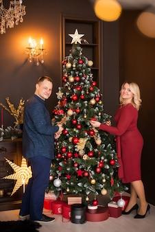 Buon natale e buone feste. famiglia, uomo e donna decorano l'albero di natale