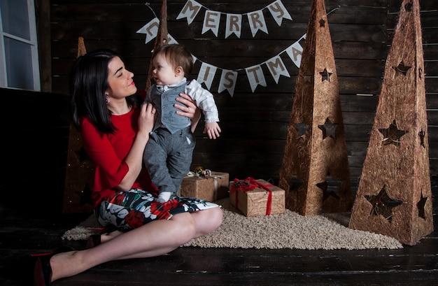 Buon natale e buone feste! mamma e suo figlio carino con doni.