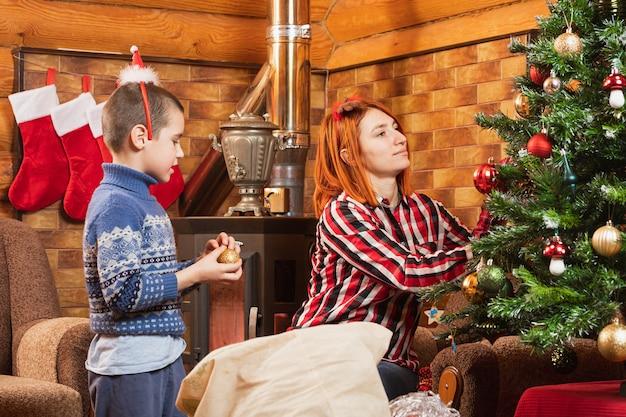 Buon natale e buone feste. mamma e figlio stanno decorando un albero di natale in un'accogliente casa di legno.