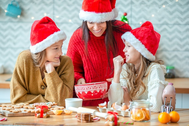 Buon natale e buone feste. madre e le sue figlie che cucinano i biscotti di natale