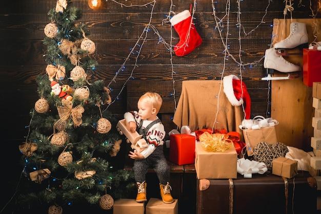Buon natale e felice anno nuovo bambini ritratto bambino con regalo su sfondo di legno bambino felice con...