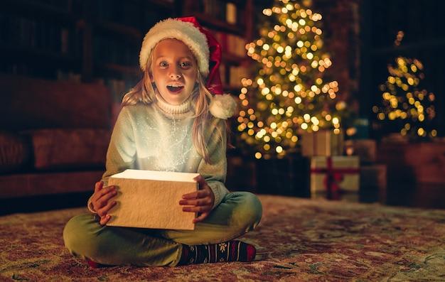 Buon natale e felice anno nuovo! affascinante bambina è seduta a casa con confezione regalo aperta. luce magica dall'interno.