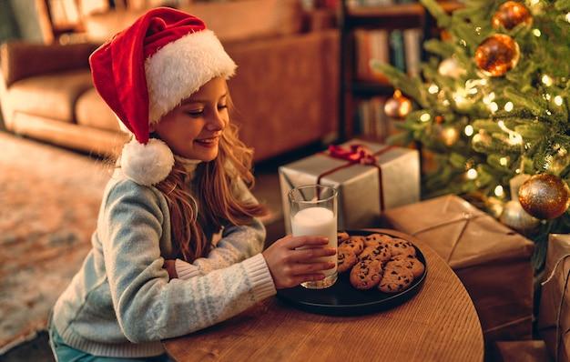 Buon natale e felice anno nuovo! affascinante bambina preparata per santa un bicchiere di latte e biscotti.