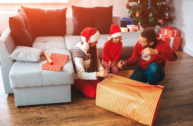 Buon natale e felice anno nuovo. la famiglia si siede sul pavimento vicino alla grande scatola del presente