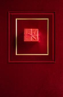 Buon natale e felice anno nuovo incandescente con un regalo di natale rosso nella cornice su velluto rosso