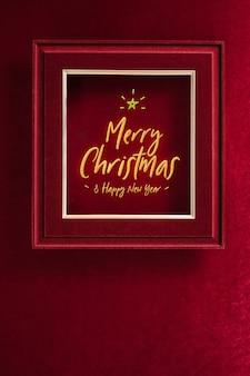 Buon natale e felice anno nuovo incandescente con stella nella cornice sulla parete in tessuto di feltro rosso velluto.