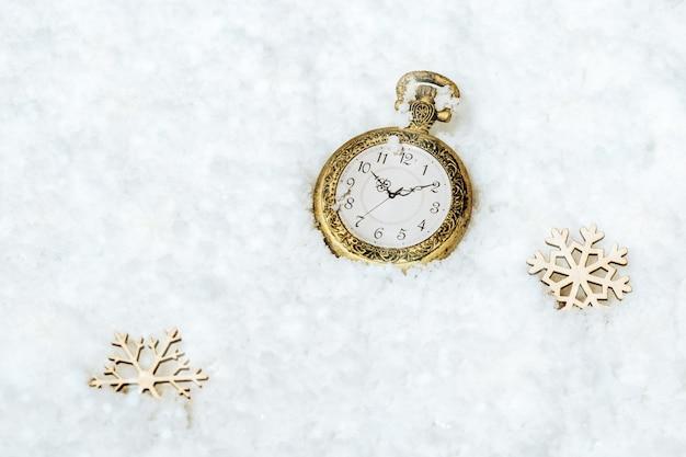 Cartolina d'auguri di buon natale e felice anno nuovo con orologio da tasca in oro vintage su sfondo di neve con fiocco di neve in legno