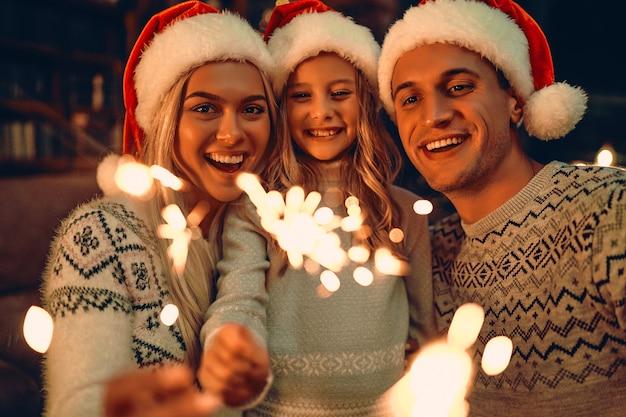 Buon natale e felice anno nuovo! famiglia felice che celebra le vacanze invernali a casa. i genitori e la loro figlia aspettano il natale in cappelli di babbo natale con le stelle filanti in mano.