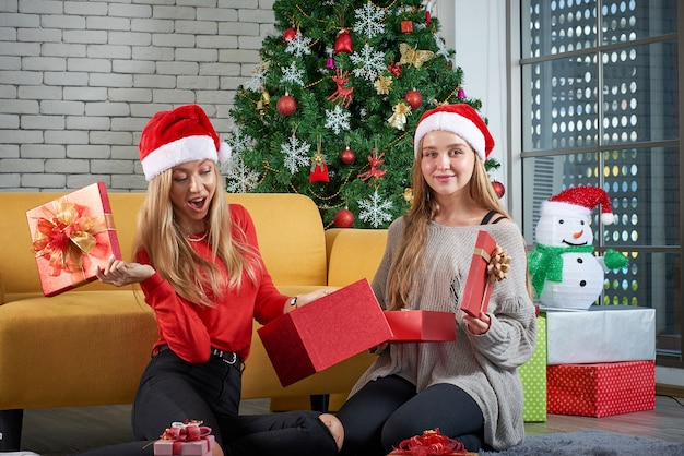 Buon natale e felice anno nuovo vacanze, bella femmina caucasica bianca festeggiare, scambiare doni rilassarsi davanti a un divano giallo e albero di natale in camera