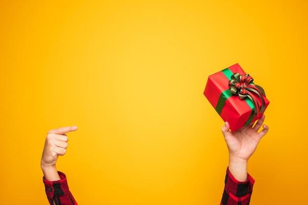 Buon natale e felice anno nuovo mani maschii che indicano la presente confezione regalo