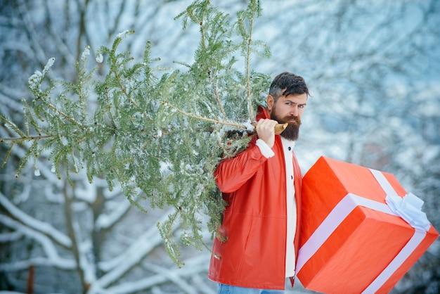 Buon natale e felice anno nuovo. l'uomo è felice per il nuovo anno. babbo natale hipster. uomo di natale su sfondo bianco neve.