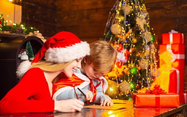 Buon natale e felice anno nuovo. madre e figlio che scrivono una lettera a babbo natale. cultura del dono.