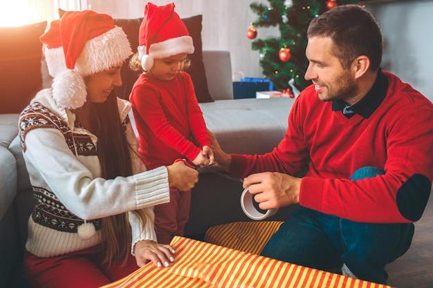 Buon natale e felice anno nuovo. bella foto di famiglia che prepara regali insieme. la ragazza e il giovane tengono insieme il nastro. la donna lo ha tagliato con le forbici. sembrano carini e positivi.
