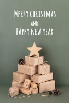 Cartolina di buon natale e felice anno nuovo. albero di natale astratto da scatole in carta artigianale, spago, forbici, coni su sfondo verde, primo piano. concetto di natale o capodanno.