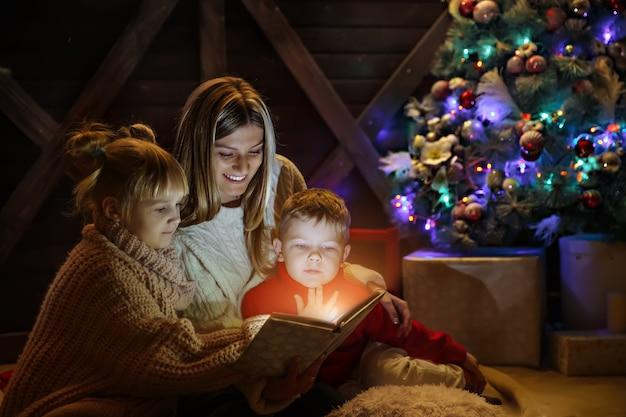 Buon natale e felice anno nuovo, madre abbastanza giovane che legge un libro a sua figlia e figlio vicino all'albero di natale.