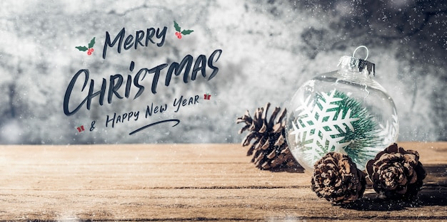 Buon natale e felice anno nuovo segno con pallina di albero di natale e pigna sul tavolo di legno con muro di cemento per celebrare lo sfondo della cartolina d'auguri di festa