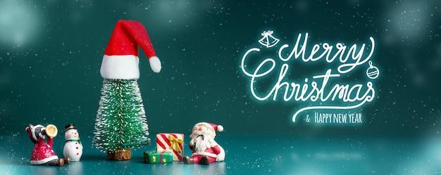 Buon natale e felice anno nuovo la neve che cade con l'albero e il pupazzo di neve di babbo natale sfondo verde