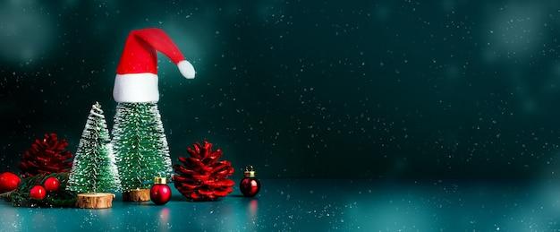 Buon natale e felice anno nuovo neve che cade con albero di natale e cappello rosso di babbo natale su sfondo verde scuro. spazio banner mockup per la visualizzazione di prodotto o design o testo